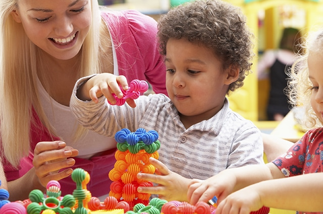 Nursery teacher playing with children