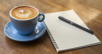 Coffee and notebook on table