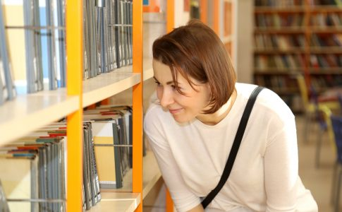 Girl looking at books in library