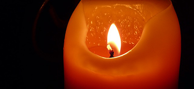 Image of candle lit in the dark