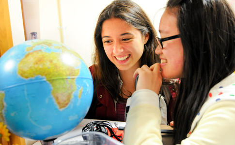 International students looking at globe