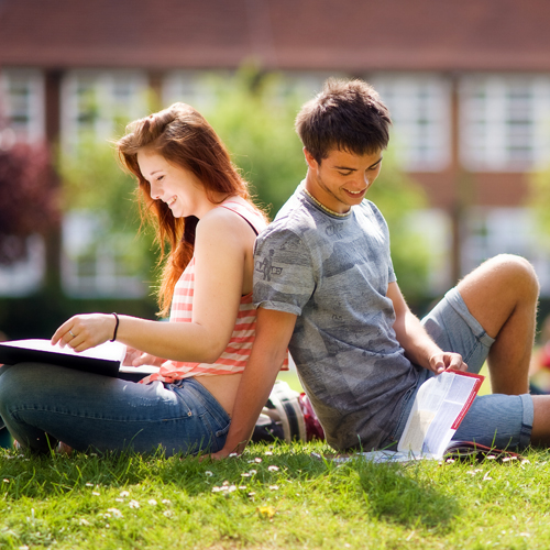 Students reading on lawn during summer